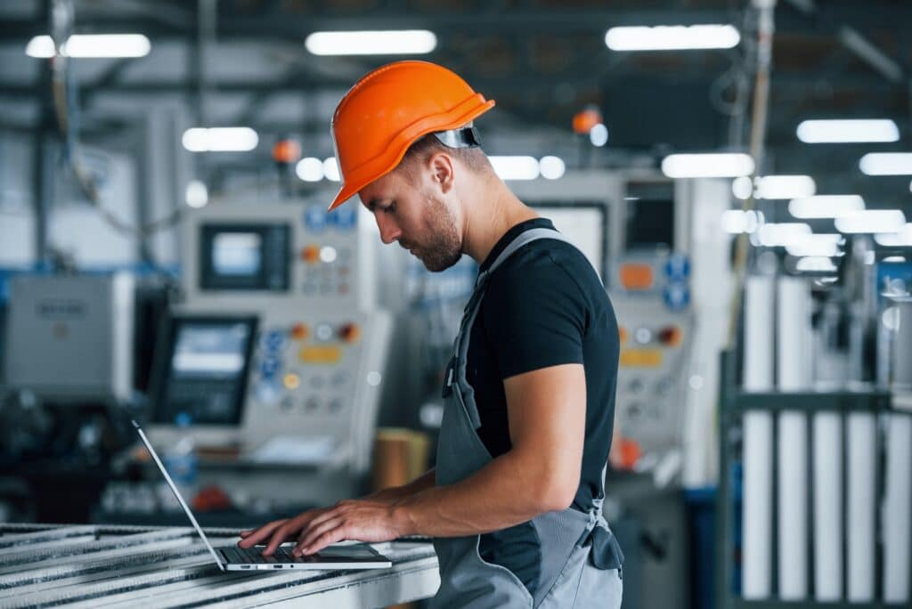 Typing on keyboard. Industrial worker indoors in factory. Young technician with orange hard hat